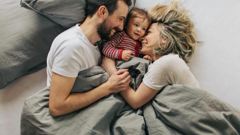 parents cuddling toddler in bed